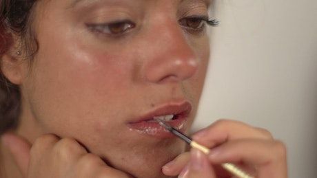 Model having makeup applied to lips