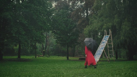 Model with an umbrella nearby in a forest full of trees