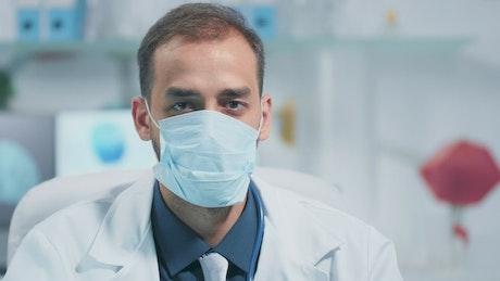Modern hospital doctor in face mask nodding