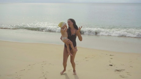 Mom and daughter dancing in the beach