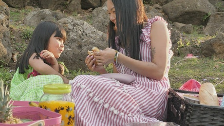 Mom and daughter eating croissant on picnic day