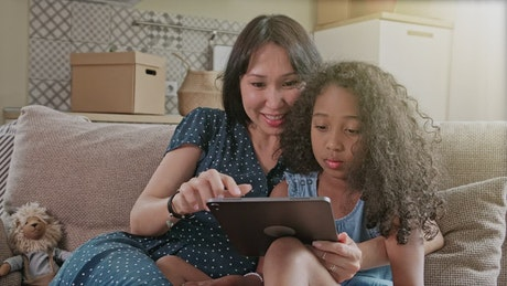 Mom and daughter spending time together with a tablet