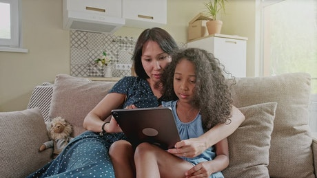 Mom and daughter use tablet on sofa in new apartment