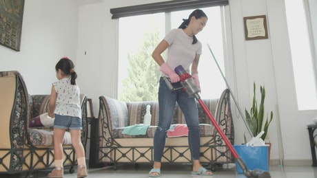Mom and daughter with vacuum cleaners cleaning a room