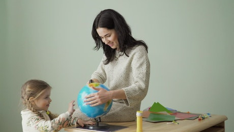Mom and young daughter spin world globe