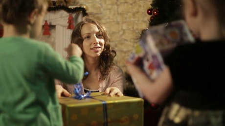 Mom giving Christmas gifts to her children