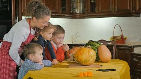 Mom helps kids prepare Jack-O-Lantern pumpkin  in kitchen