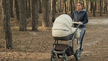 Mom strolling her baby in a stroller in the forest