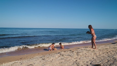 Mom taking photos of her daughters' sand pyramids