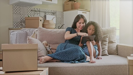 Mom teaching something to her daughter on a tablet
