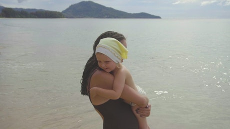 Mom with a daughter walking on the sandy beach