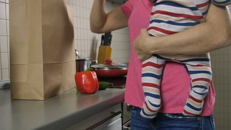 Mom with her baby in her hands starts cooking