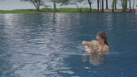 Mom with her daughter in the pool