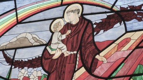 Monk carrying a child depicted in the stained glass window of a church
