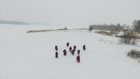 Monks walking through the snow