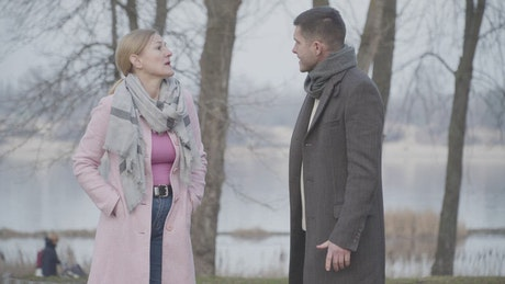 Mother and adult son quarrel on cold day in park