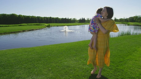 Mother and child by a lake fountain