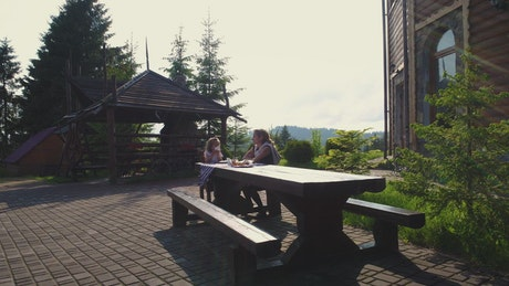 Mother and daughter at lunch on an outdoor bench
