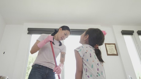 Mother and daughter cleaning their house