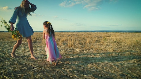 Mother and daughter play happily in a dry field