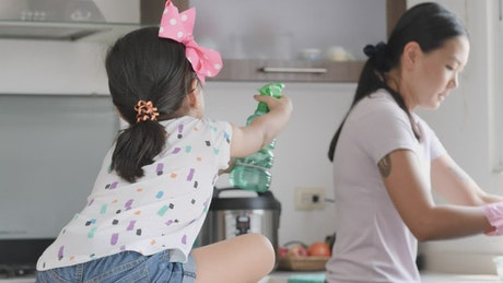 Mother and daughter playing happily in the kitchen