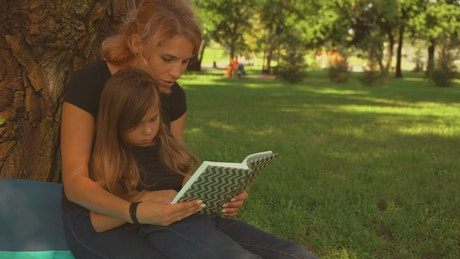 Mother and daughter read a book together in a park