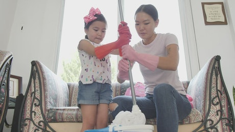 Mother and daughter squeezing a mop together