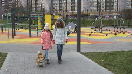 Mother and daughter walking through the park