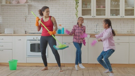 Mother and daughters in a kitchen dancing