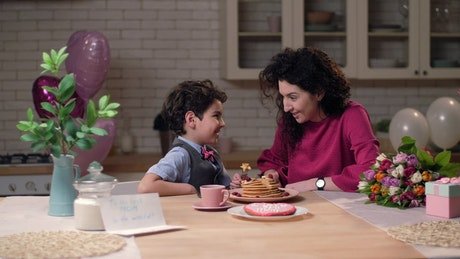 Mother and son sharing pancakes