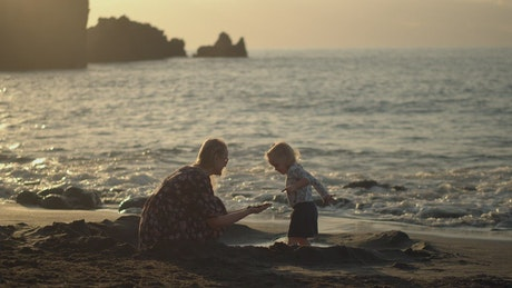 Mother and young child playing with sand