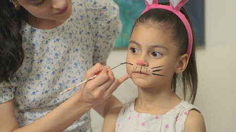 Mother draws rabbit whiskers to her daughter