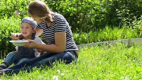 Mother feeding her child outside