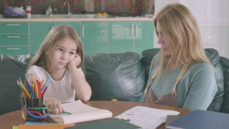 Mother helps her daughter study