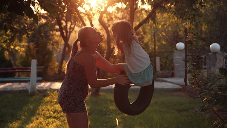 Mother kissing her daughter on the tire swing