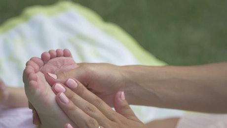 Mother massaging baby feet