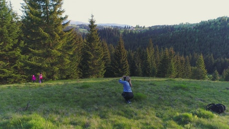 Mother photographing her daughters in nature