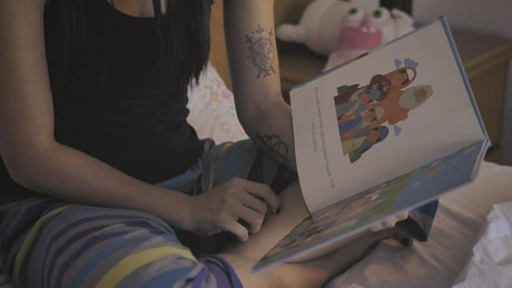 Mother reading a book to her little daughter before bed
