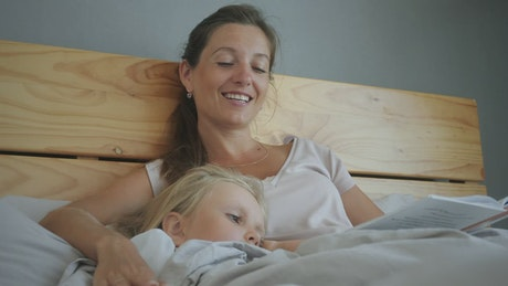 Mother reading a story to daughter in bed