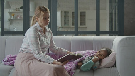 Mother reads a book to her sick daughter