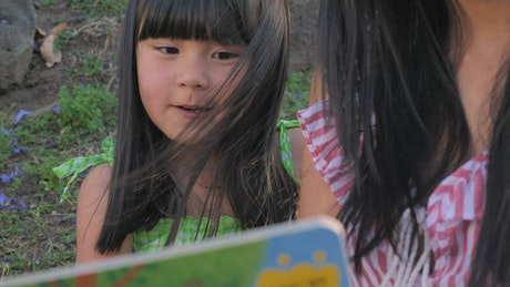 Mother reads a story to her daughter outdoors