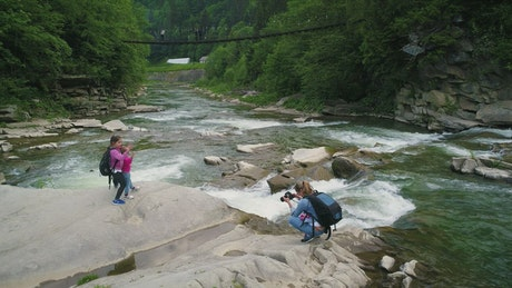 Mother taking photos of her daughters in a river