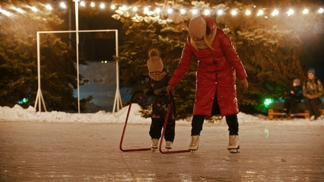 Mother teaching her daughter to ice skating