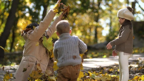 Mother throwing leaves at her kids