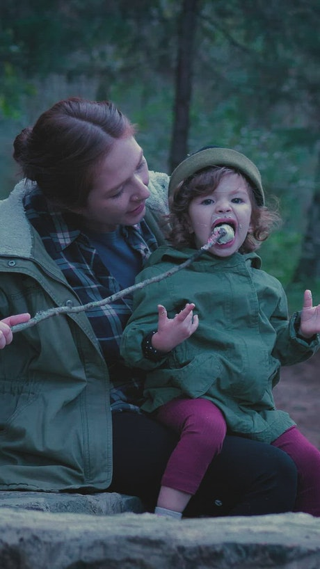 Mother with her little daughter eating a marshmallow in nature