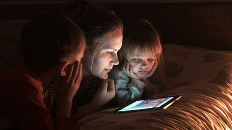 Mother with two children watching the tablet