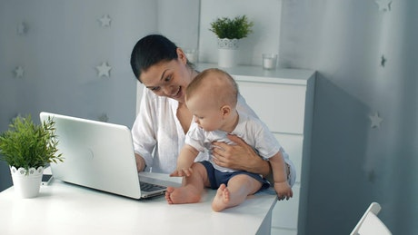 Mother working on her laptop with her son