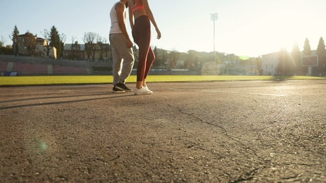 Motivated couple lunge at start of race on outdoor track