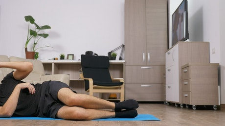 Motivated man exercises on floor at home
