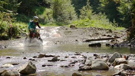 Motocross rider crosses a river in the mountain